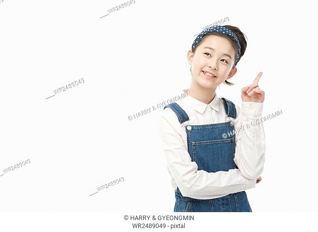 Portrait of smiling Korean school girl standing her index finger looking up