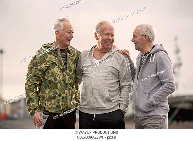 Senior friends wearing sports clothes arms around each other smiling
