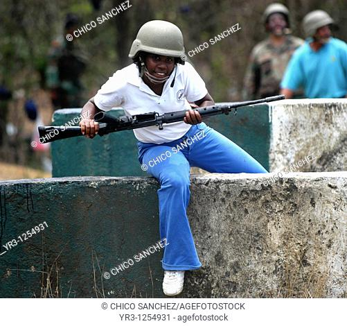 An army reservist runs through an obstacle course during military training in Charallave, Venezuela