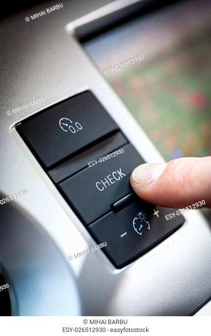 finger pushing the check button inside a car