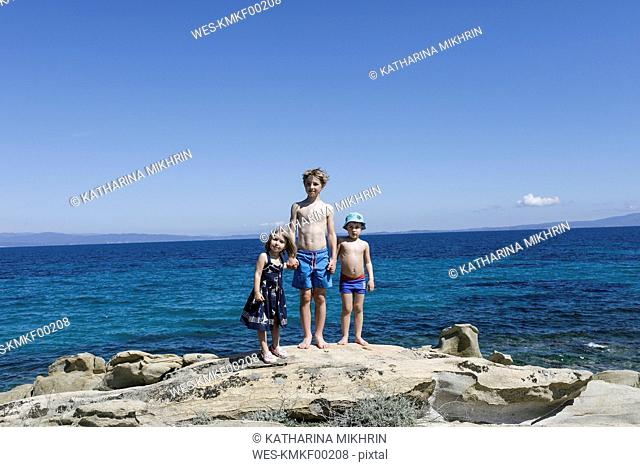 Greece, Chalkidiki, three children stamnding hand in hand on rock in front of the sea