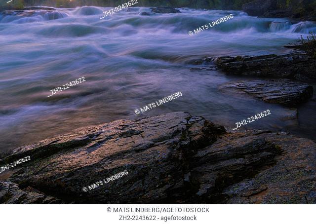 Kamajokk river in Kvikkjokk, sun reflecting on rock in forground, Swedish lapland