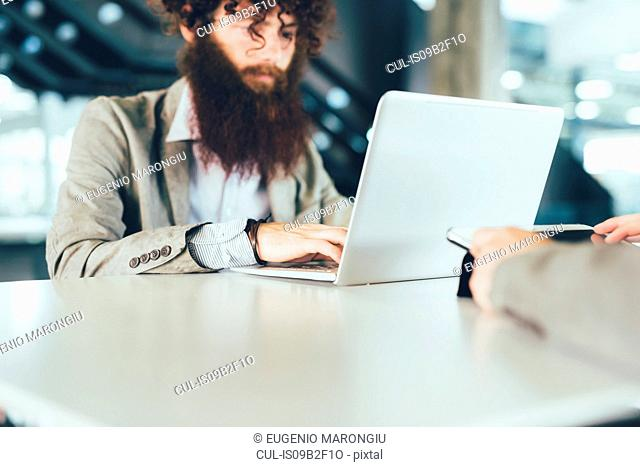 Young male hipster using laptop at desk