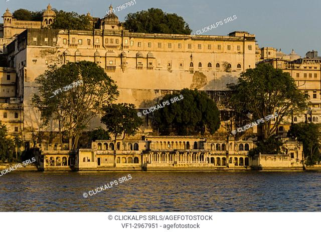 Udaipur, Rajasthan, India. The Udaipur City Palace at sunset seen from the shores of the Pichola Lake