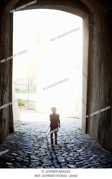 Young child walking towards a light opening