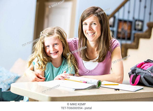 Smiling mother and daughter (8-9) sitting at table studying