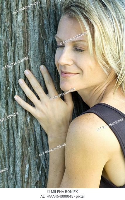 Woman leaning against tree trunk, eyes closed, smiling, cropped view, full frame