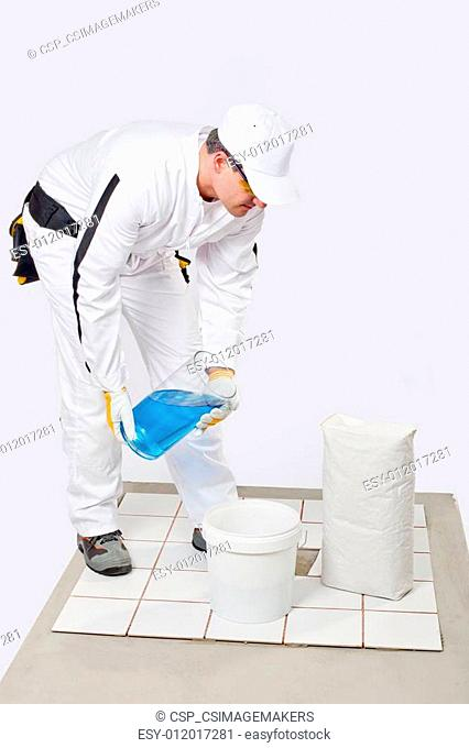 Worker mix tile adhesive bucket of water