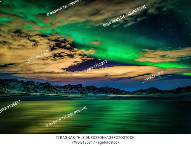 Aurora Borealis over Lake Kleifarvatn, Iceland. Cloudy evening with northern lights reflecting on the lake