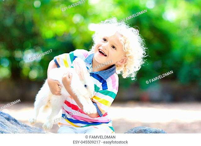 Child playing with white rabbit. Little boy feeding and petting white bunny. Easter celebration. Egg hunt with kid and pet animal