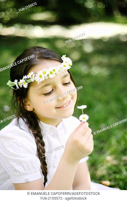 Little girl with crown of daisies and daisies in hand