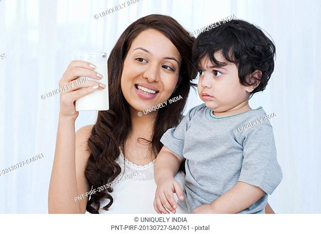 Smiling woman showing milk to her son