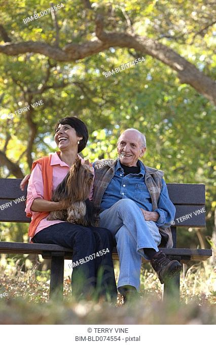 Senior couple in park with dog