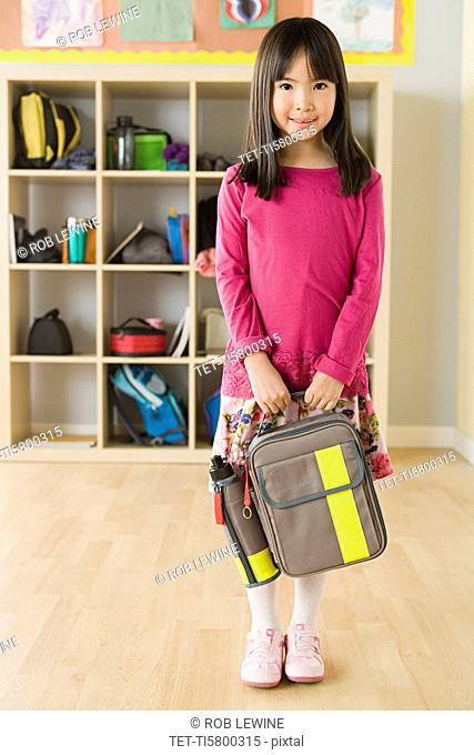 Portrait of schoolgirl 6-7 holding backpack