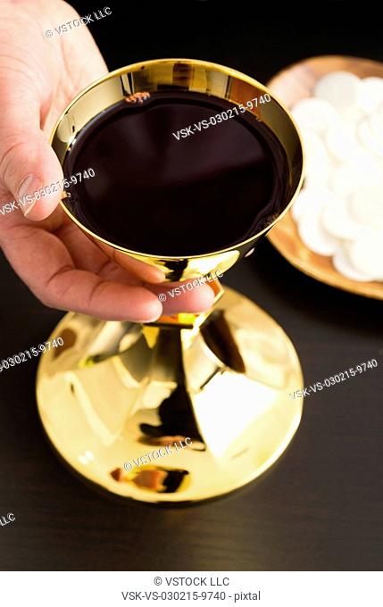 Christian holy communion, man's hand holding gold chalice with wine, communion wafer on plate