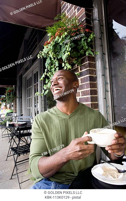 Portrait of a laughing young man holding a coffee cup at a sidewalk cafi