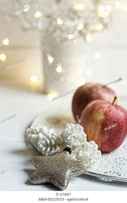 Christmas Still Life with golden star, apples and white cones on plates, fairy lights in the background
