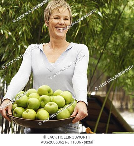 Mature woman holding a bowl of apples