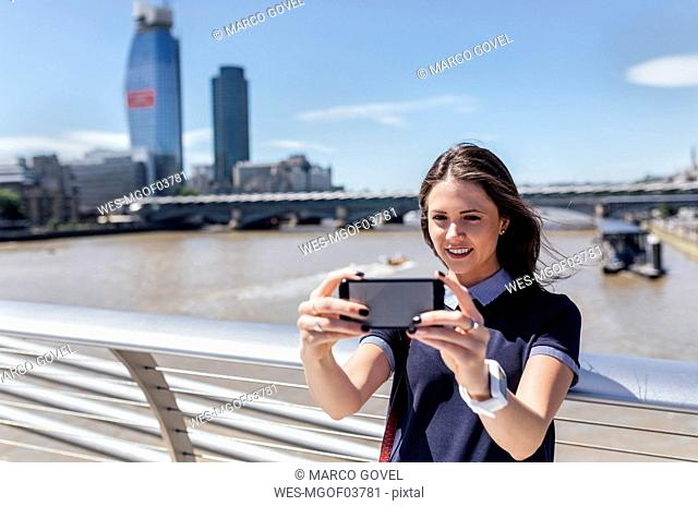 UK, London, woman taking a selfie on the Millennium Bridge