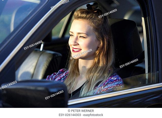 a brunette woman sitting in a car and smiles