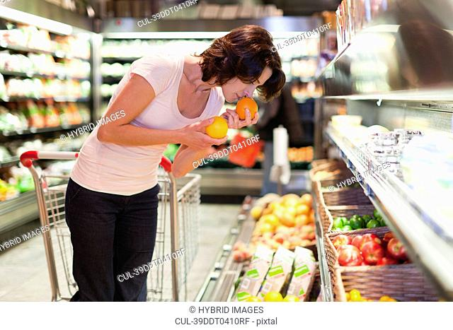 Woman smelling fruit at grocery store