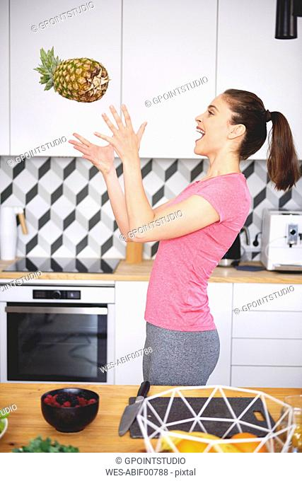 Young woman throwing pineapple in the air in the kitchen