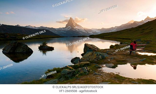 Europe, Switzerland, canton of Valais, Visp district, Zermatt, Stellisee lake - hiker admires the Matterhorn at sunset
