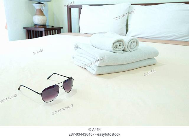 Towels placed on the bed. Sunglasses are placed side by side on site
