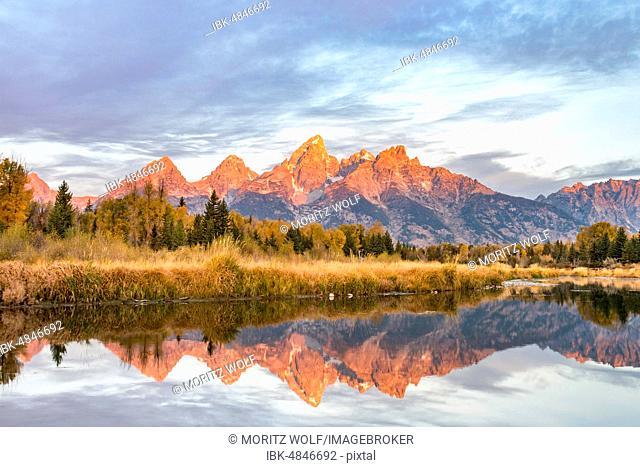 Mountains glow red at sunrise, Grand Teton Range mountain range reflected in the river, autumn landscape on Snake River, Schwabacher Landing