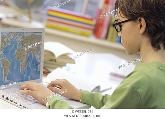 Boy (8-9) using laptop, side view