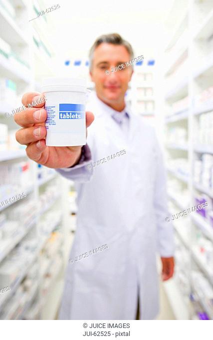 Pharmacist holding bottle of prescription medication in pharmacy