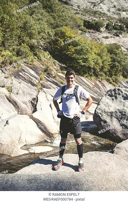 Spain, A Capela, portrait of smiling cross-country runner standing on a rock