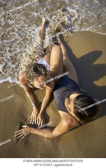 Two young women relaxing on beach. Chersonissos, Crete, Greece