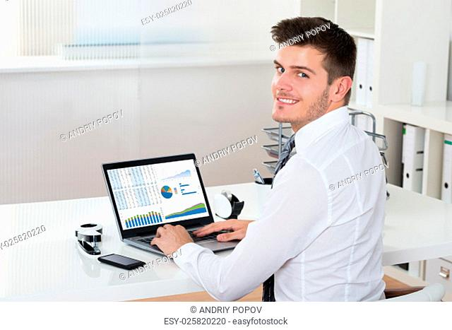 Young Happy Businessman Analyzing Financial Statistics On Laptop At Desk
