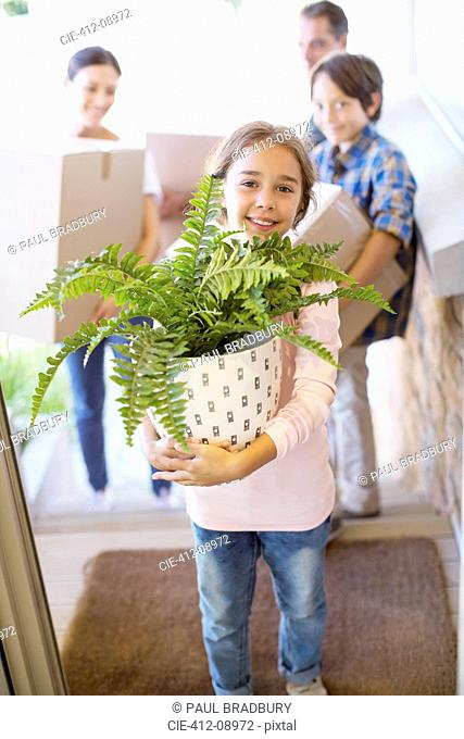 Portrait of smiling family moving belongings into house