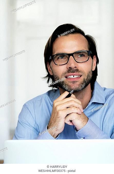 Smiling businessman wearing glasses and holding pen