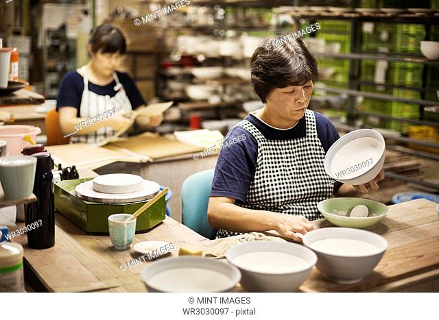 Two women sitting in a workshop, working on Japanese porcelain bowls