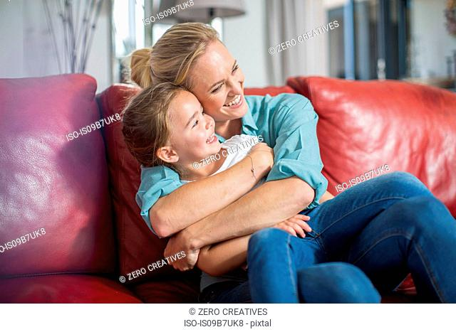 Mother and daughter on sofa cuddling and smiling