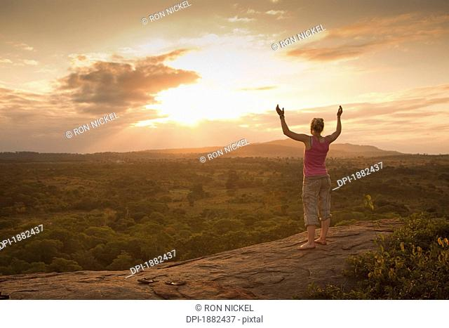 A Young Woman Looking Over The African Landscape With Arms Raised, Manica, Mozambique, Africa