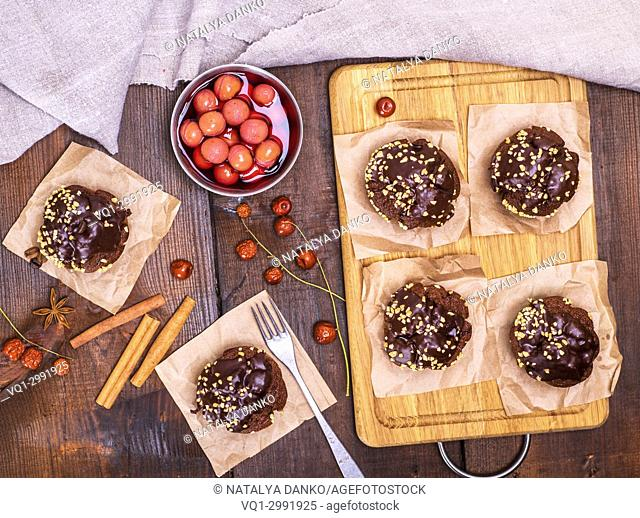chocolate muffins and a plate of cherries in their own juice on a brown wooden background, top view