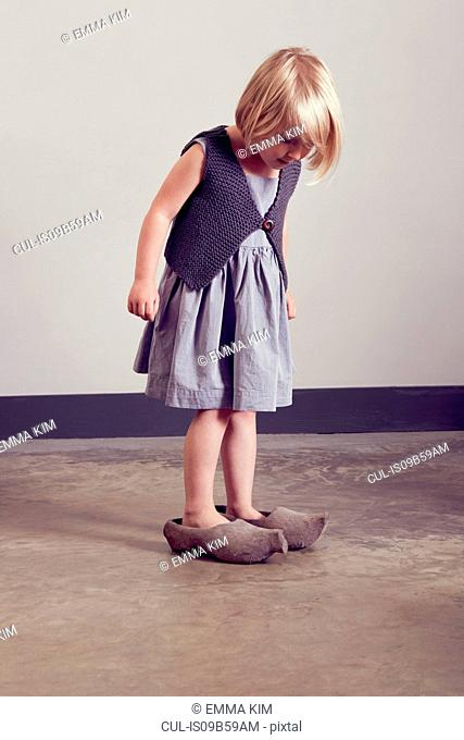 Girl standing in vintage wooden clogs looking down