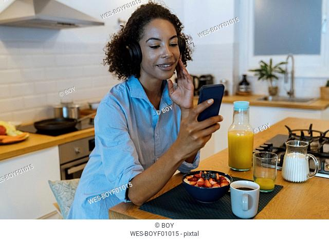 Woman with headphones, using smartphone in her kitchen