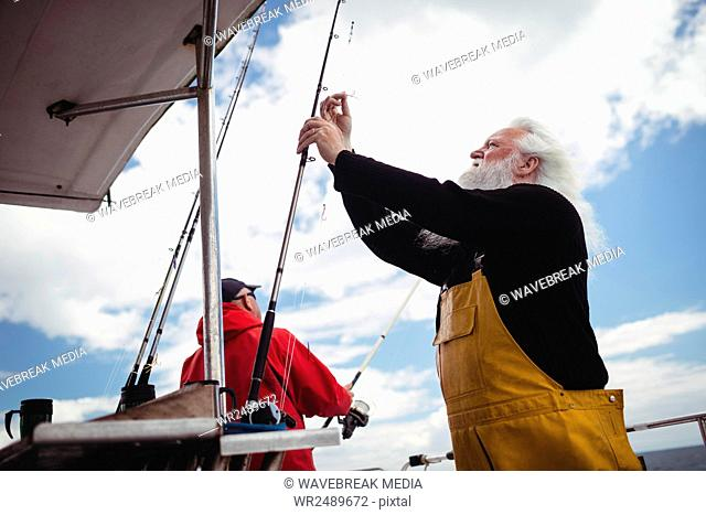Fisherman preparing fishing rod