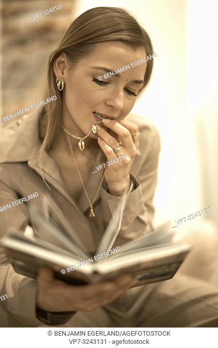 fashionable blogger woman reading book indoors, expensive jewellery necklace chain in mouth, rich, wealthy woman, in Munich, Germany