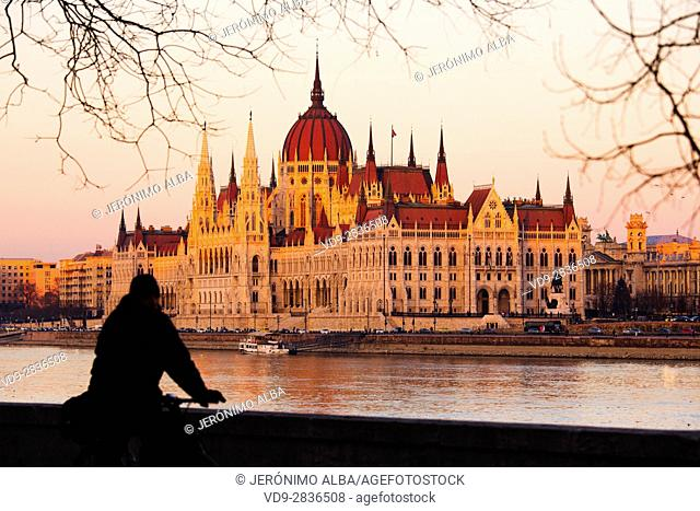 Silhouette of a man on a bicycle. Hungarian Parlament building, Neogothic Style, National Assembly. Banks of Danube river