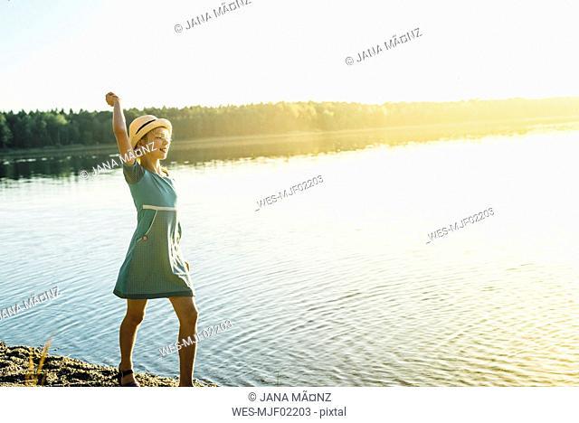 Girl wearing summer dress and hat posing at lakeshore