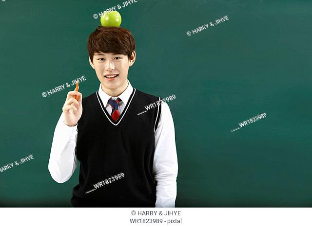 A student with an apple on his head
