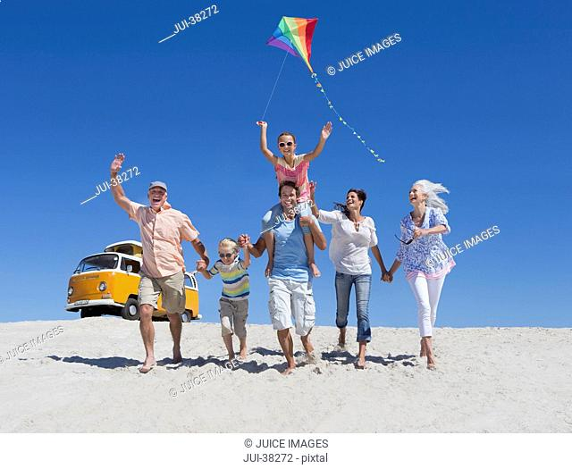 Happy multi-generation family with kite running and waving on sunny beach with van in background