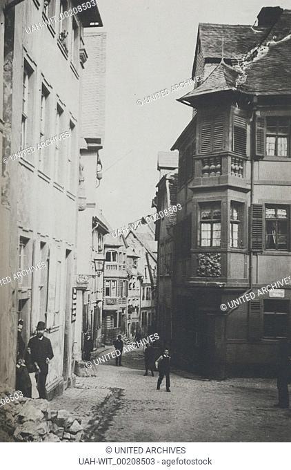 """Heringsbrunnengasse in Mainz von der Weißliliengasse her gesehen. Das Eckhaus rechts (""""""""Zum Hering"""""""") sowie die Nachbargebäude existieren heute nicht mehr"""