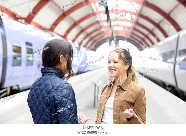 Female friends communicating on railway station